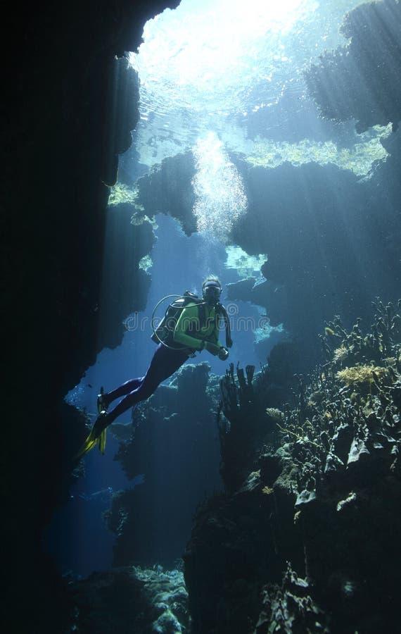 Zambullidor de equipo de submarinismo en una cueva con los rayos de sol foto de archivo libre de regalías