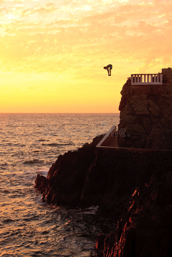 Zambullidor del acantilado de la costa de Mazatlan en la puesta del sol fotos de archivo libres de regalías