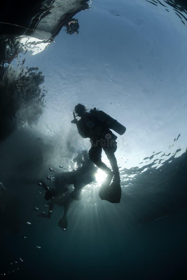 Zambullidores de equipo de submarinismo en silueta foto de archivo libre de regalías