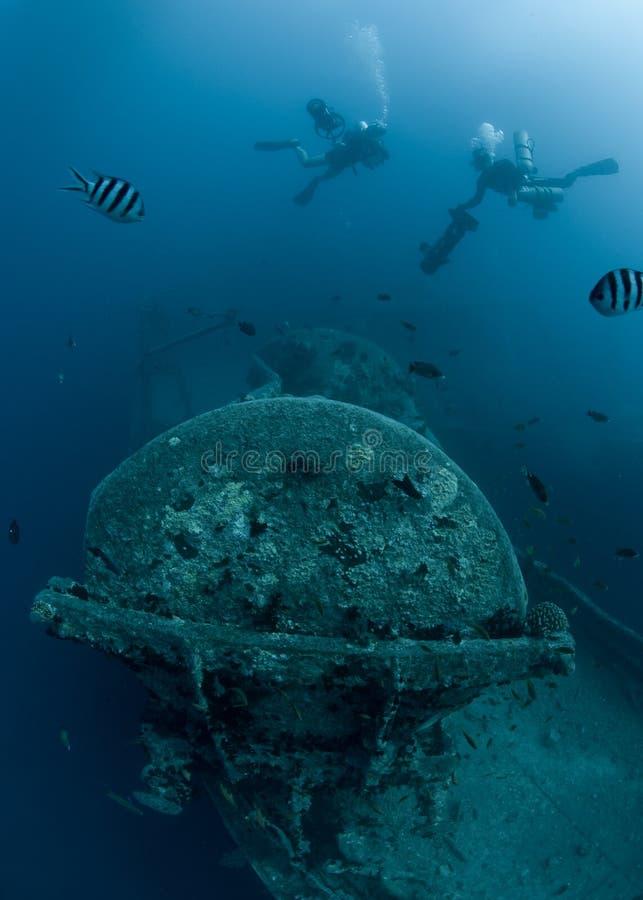 Zambullidores de equipo de submarinismo que exploran el naufragio SS Thistlegorm imagen de archivo