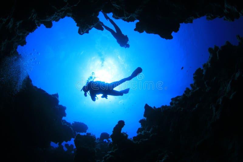 Zambullidores de equipo de submarinismo sobre caverna fotos de archivo
