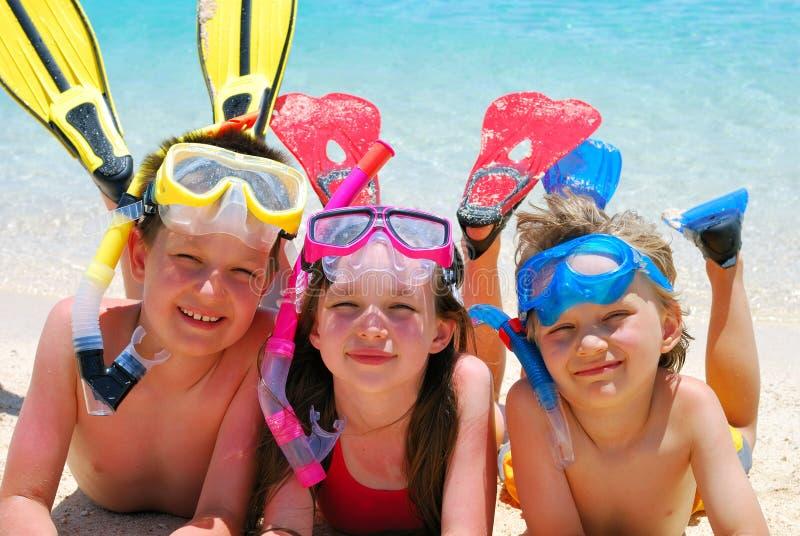 Zambullidores felices en una playa imágenes de archivo libres de regalías