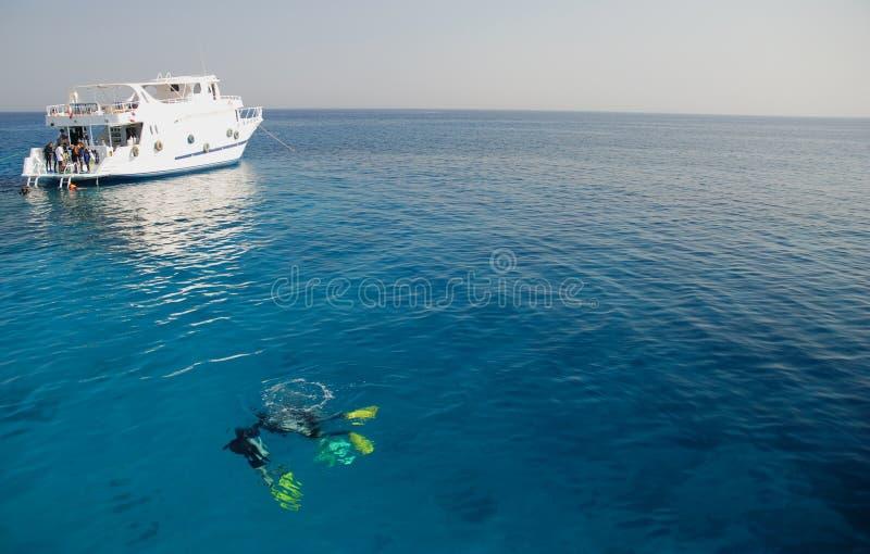 Zambullidores y barco en el Mar Rojo imagenes de archivo