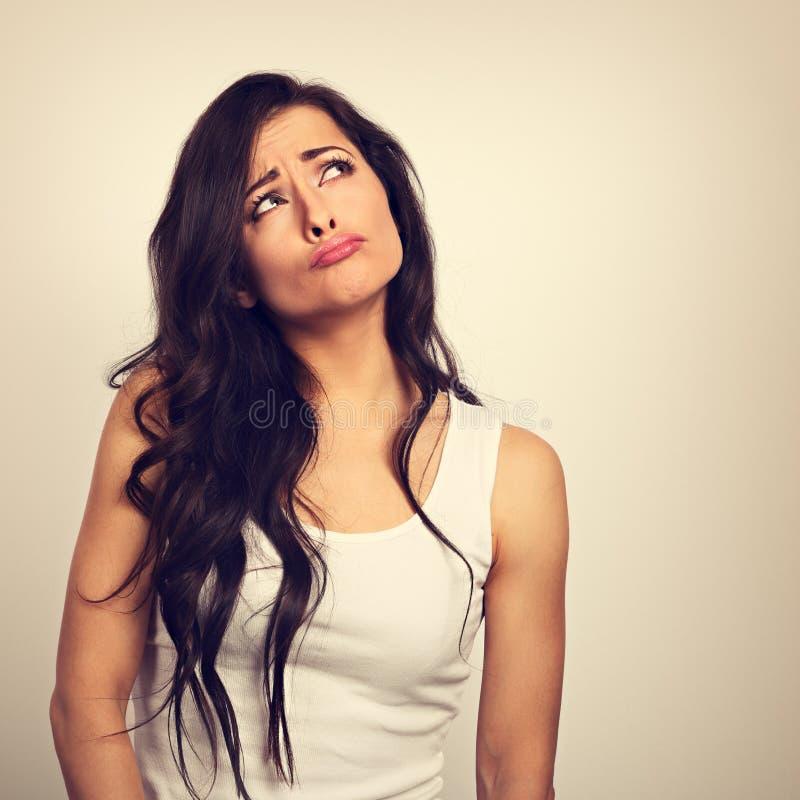 Zamieszanie brunetki kobiety grimacing poważni patrzeć i główkowanie zdjęcia royalty free