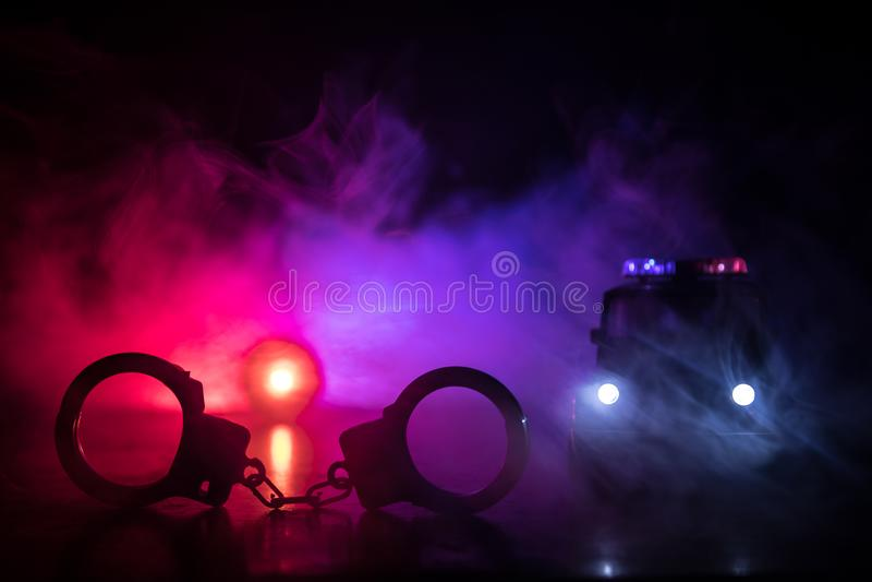 Zamknięci kajdanki na ulicznym bruku przy nocą z samochodem policyjnym zaświecają fotografia stock