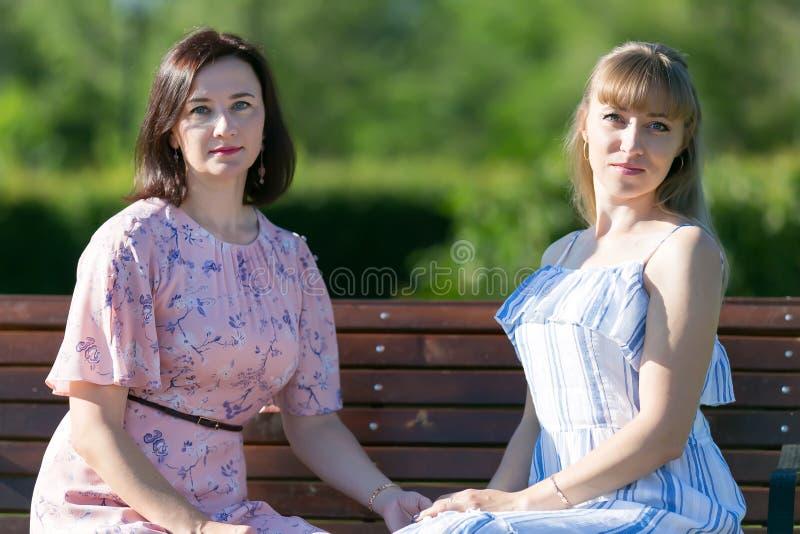 Zamknięci przyjaciele siedzą na ławce w miasto parku obrazy stock