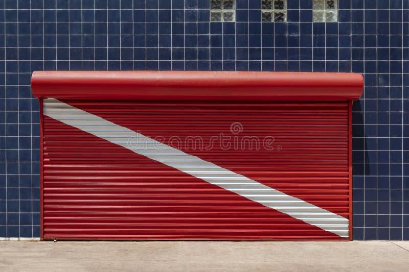 Zamknięta sklep żaluzja malująca czerwona akwalungu pikowania flaga z wal fotografia stock