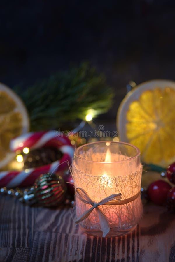 Zamkniętego widoku Magiczni boże narodzenia dekorowali Płonącą świeczkę na drewnianym nieociosanym tle obraz stock