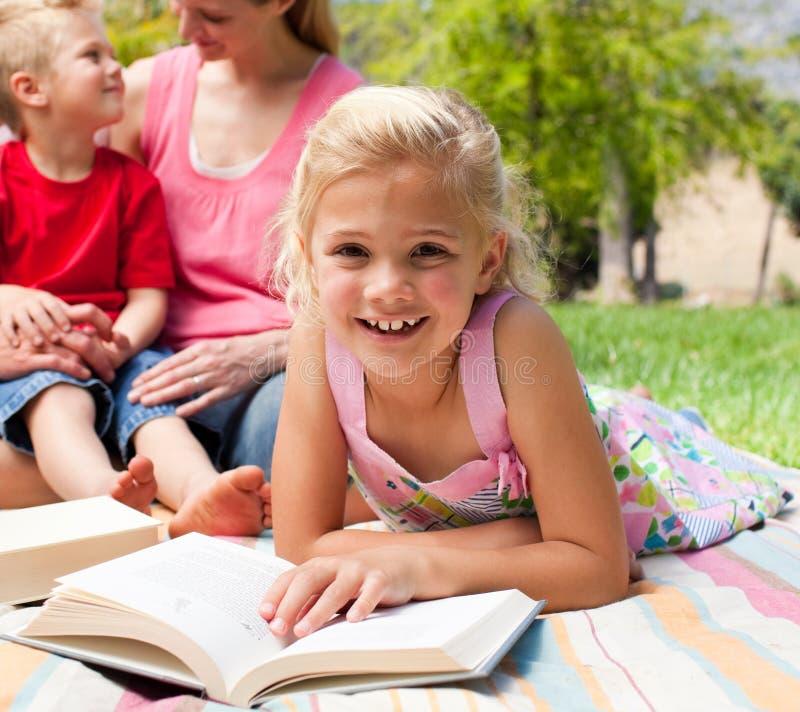 zamkniętej dziewczyny mały pykniczny czytanie pykniczny fotografia stock