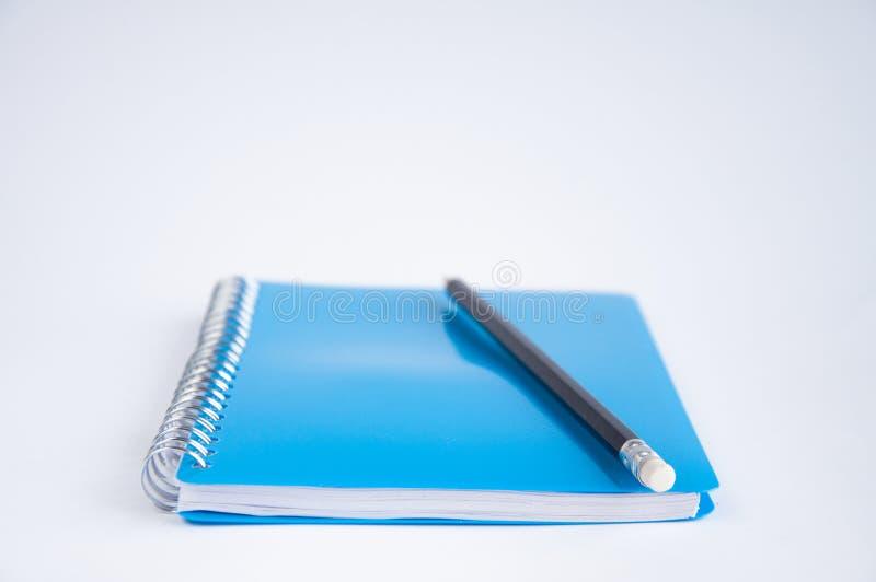 Zamknięty błękitny notatnik na stole Na notatniku jest czarny ołówek obrazy stock