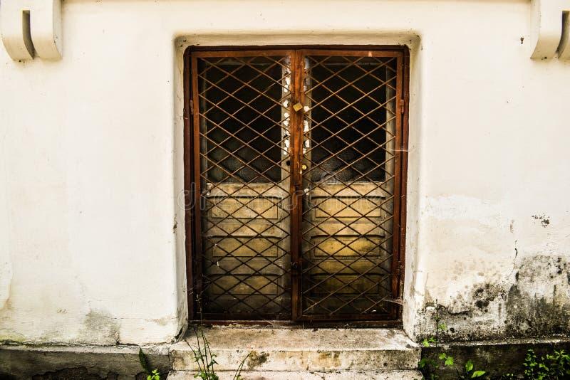 Zamknięty drzwi z żelazo płotowymi utrzymuje sekretami wśrodku grunge budynku w niedozwolonym miejscu zdjęcie stock