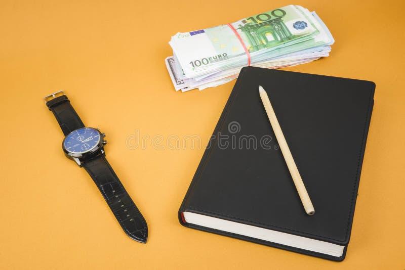 zamknięty notepad, zegar, gotówka i ołówek kłaść na nim na biurowym pomarańcze stole, obraz stock