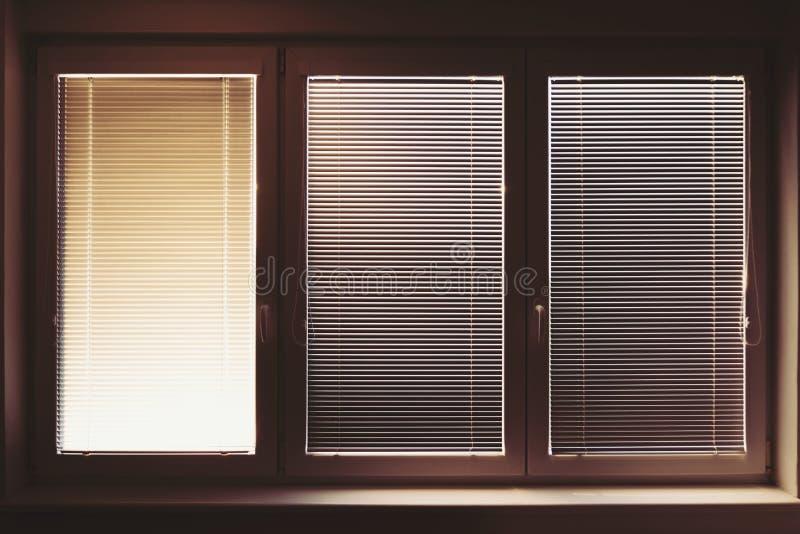 Zamknięty plastikowy okno na słonecznym dniu z horyzontalnymi plastikowymi storami fotografia stock
