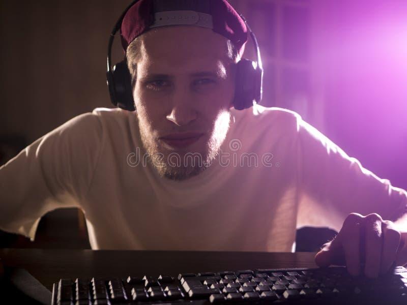 Zamknięty portret młody brodaty mężczyzna bawić się wideo grę na komputerze w nocy w domu obrazy stock