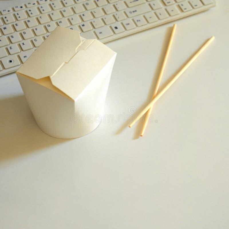 Zamknięty pudełko Wok kluski Koreańczyk, japończyk, chińczyków chopsticks obok komputerowej klawiatury na białym tle lub jedzenie zdjęcia stock