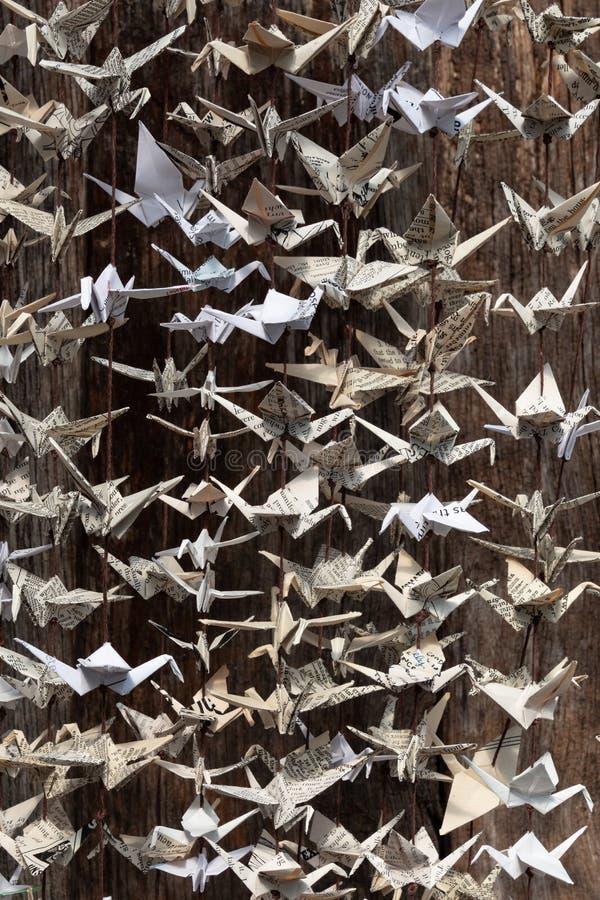 Zamknięty widok fałdowi origami papieru żurawie wiesza od sznurków, stary drewniany tło zdjęcia stock