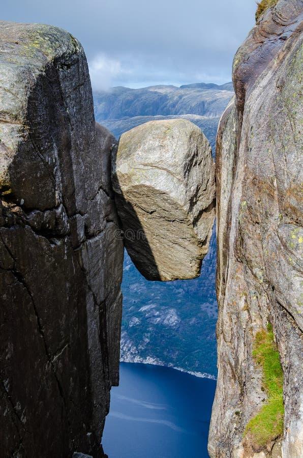 Zamknięty widok Kjeragbolten skała z błękitnym fjord Lysefjorden w tło sposobie zdjęcia stock