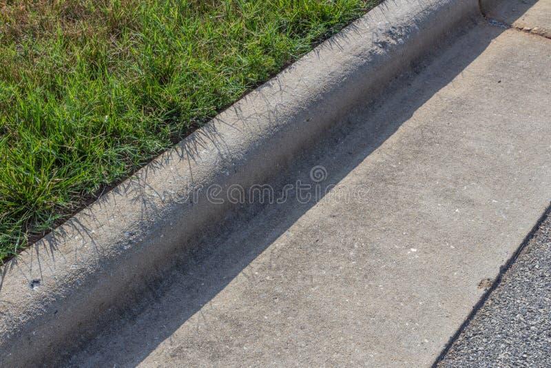 Zamknięty widok krawężnik, zielona trawa i asfalt tworzący betonowi, obrazy royalty free