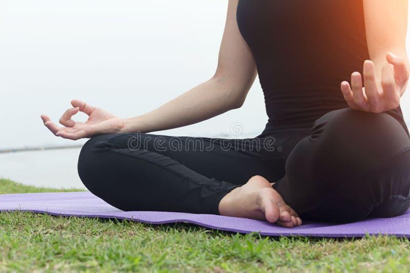 zamknięty zamknięta ręka Kobieta robi joga plenerowy Kobieta ćwiczy joga przy dennym tłem Pojęcie zdrowy życie zdjęcie royalty free