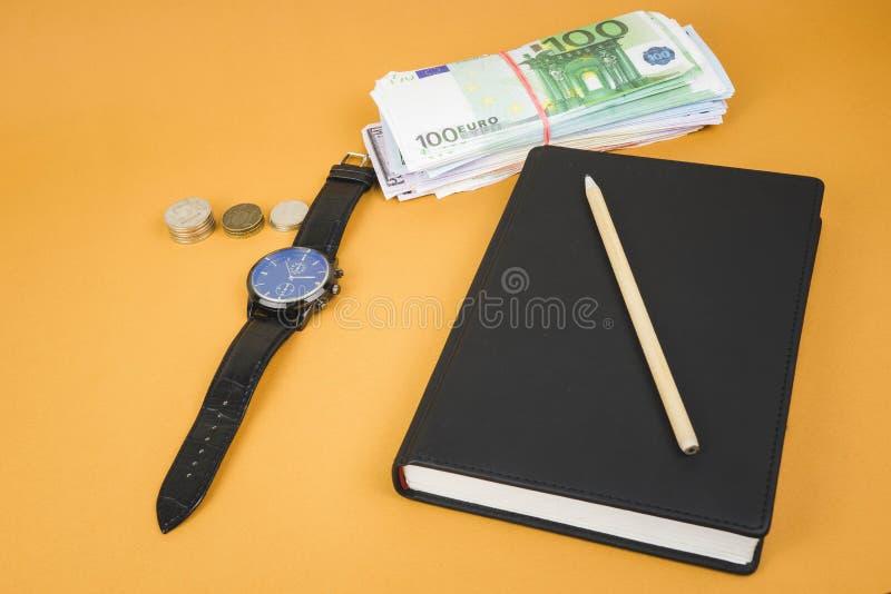 zamkni?ty notepad, zegar, got?wka i o??wek k?a?? na nim na biurowym pomara?cze stole, fotografia royalty free