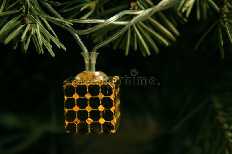 Zamknij, makro Kostka świątecznego ogródka wisząca z choinki i świeci złotym światłem obrazy stock