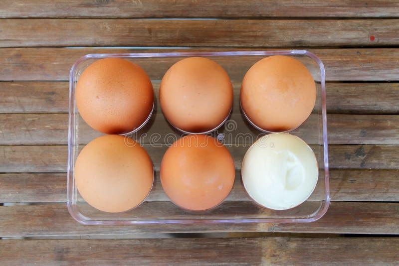 zamknij sześć brązowych jaj w plastikowym pudełku na bambusowym stole z jednym zepsutym jajem, widok z góry obraz stock