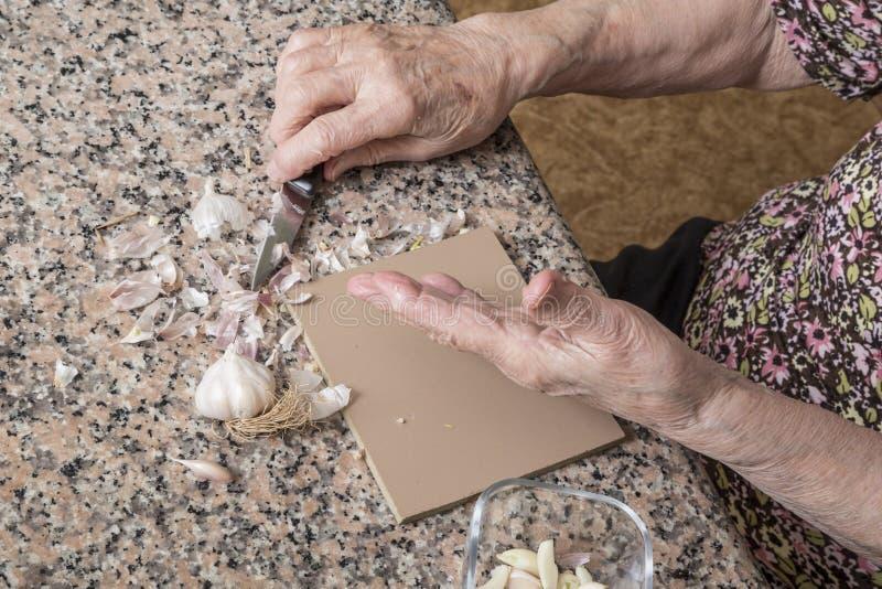 Zamknij zmarszczone ręce starszej kobiety obierającej czosnek fotografia stock