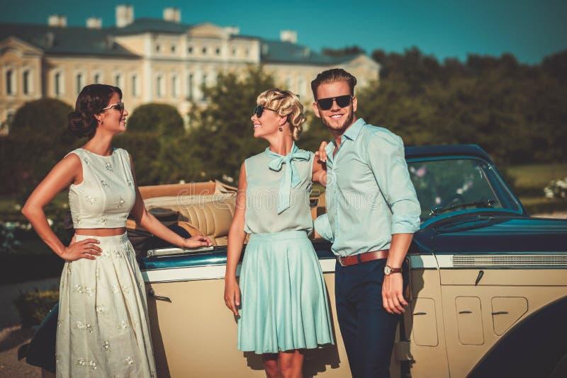Zamożni przyjaciele zbliżają klasycznego kabriolet zdjęcie royalty free