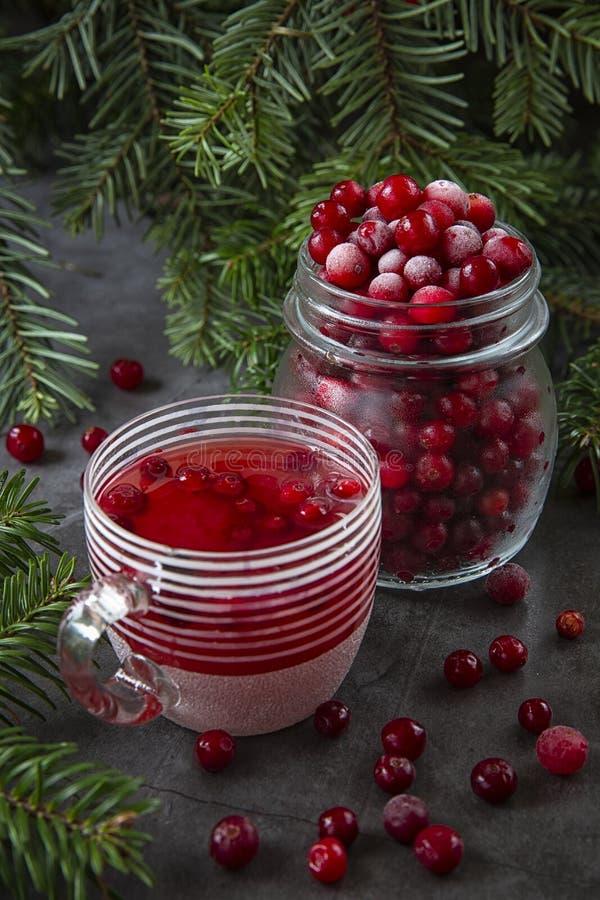 Zamrożone jagody żurawinowe w słoiku i soku żurawinowym w szklance na stole zdobionym gałęziami świąt Bożego Narodzenia fotografia stock