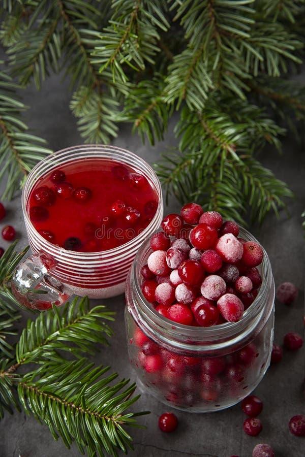 Zamrożone jagody żurawinowe w słoiku i soku żurawinowym w szklance na stole zdobionym gałęziami świąt Bożego Narodzenia obrazy royalty free