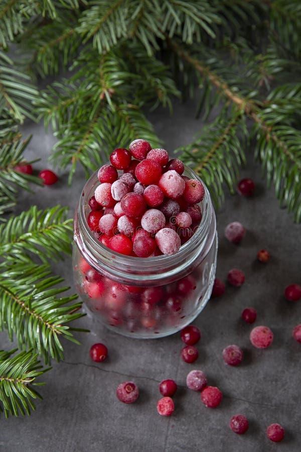 Zamrożone jagody żurawinowe w słoiku na stole zdobione gałęziami choinki Zima świąteczna fotografia stock