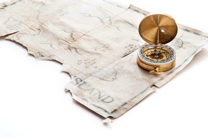 Zamyka do złocistego nautycznego kompasu na starej rocznik mapie z sfałszowaną wyspą pirata skarb obrazy stock
