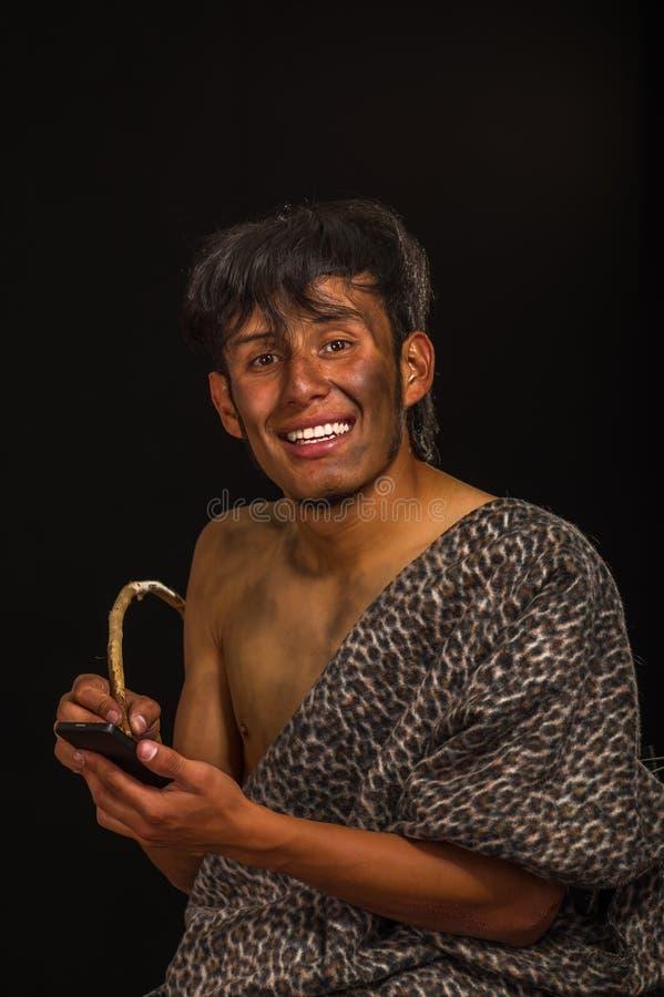 Zamyka up śmieszny prehistoryczny ono uśmiecha się, trzymać telefon komórkowego i pisać z drewnianym kijem kamera, w czerni fotografia royalty free