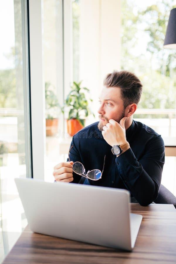 Zamyka up biznesmena brodaci szkła w przy jego laptopem, patrzeje w okno i obrazy royalty free