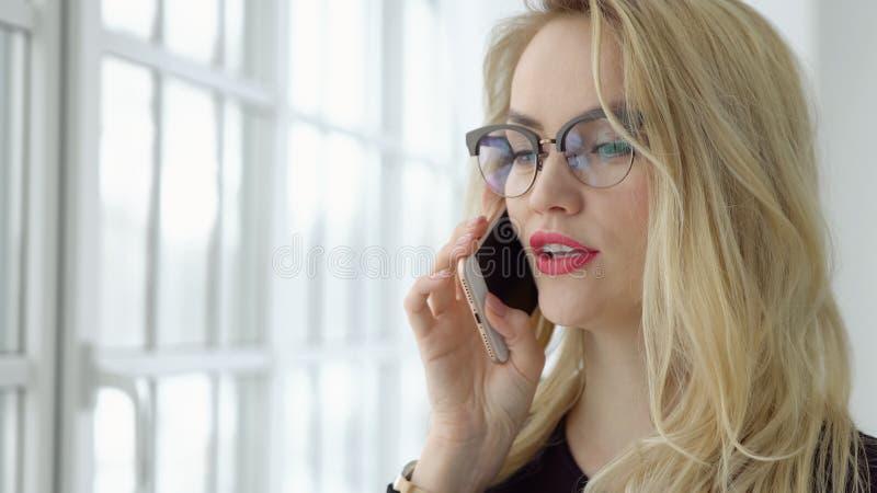 Zamyka up blondynki kobieta opowiada na telefonie okno obraz stock