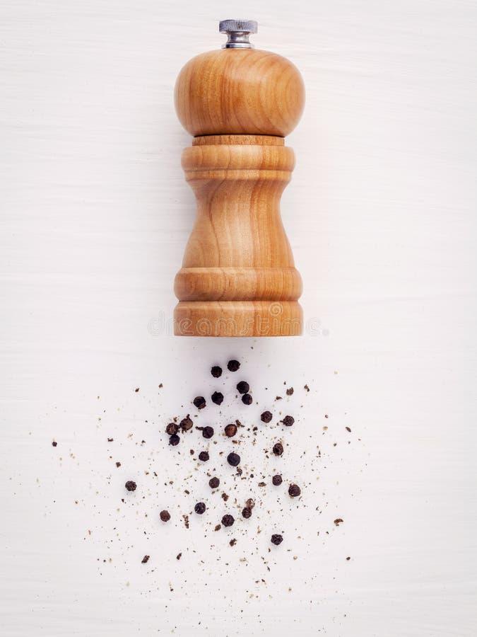 Zamyka up butelka czarny pieprzowy młyn na białym drewno stole sezon obrazy royalty free