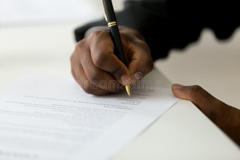 Zamyka up czarny pracownik podpisuje legalną dokumentację fotografia royalty free