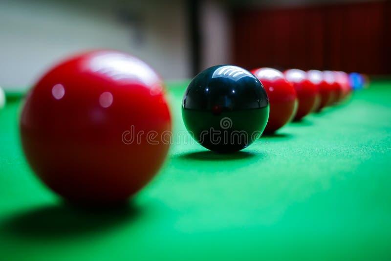 Zamyka up czerwone i czarne piłki na snookeru stole fotografia stock