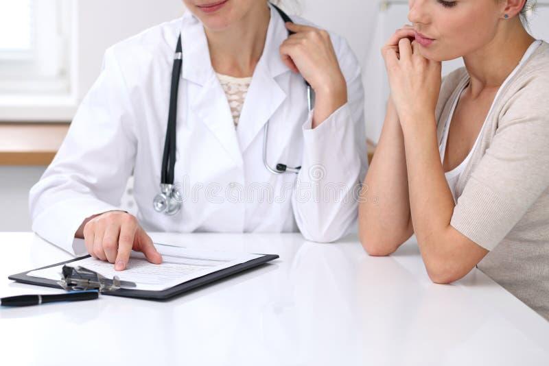 Zamyka up doktorski i cierpliwy obsiadanie przy biurkiem podczas gdy lekarz wskazuje w medyczny formularzowy hystory Medycyna a zdjęcia stock