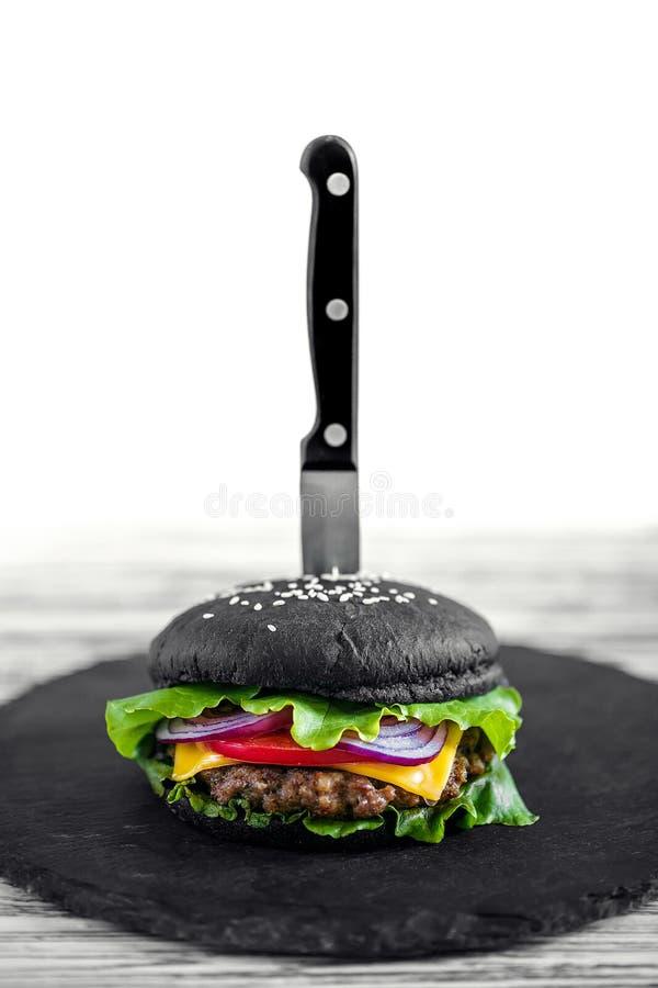 Zamyka up Domowej roboty Czarny hamburger z serem Cheeseburger z czarną babeczką na białym drewnianym tle zdjęcia royalty free