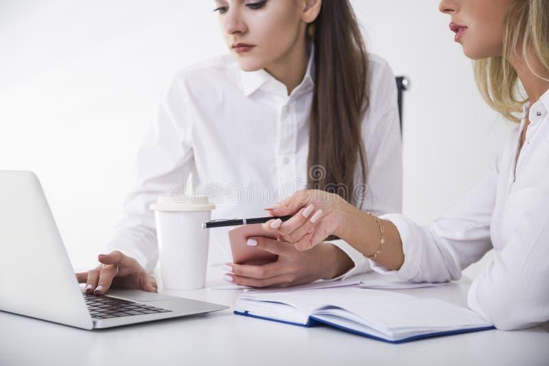 Zamyka up dwa bizneswomanu przy stołem w biurze Jeden pisać na maszynie Drugi wskazuje z jej piórem zdjęcia royalty free