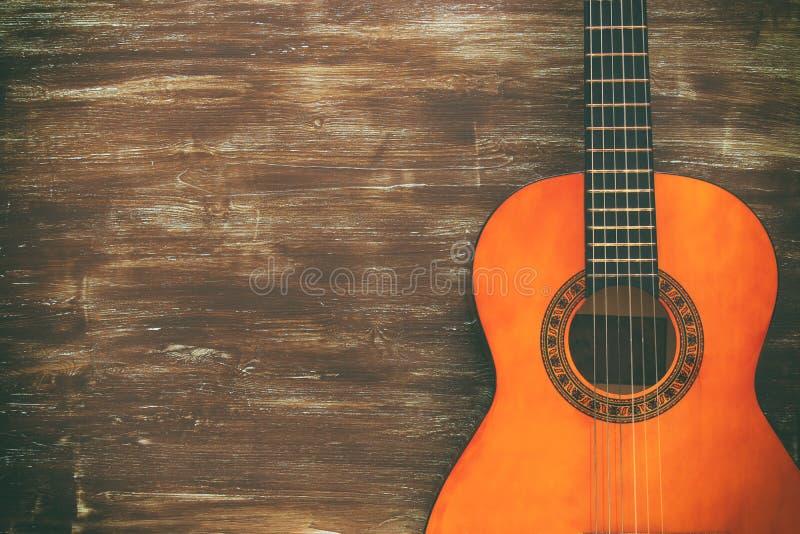 Zamyka up gitara akustyczna przeciw drewnianemu tłu zdjęcie royalty free