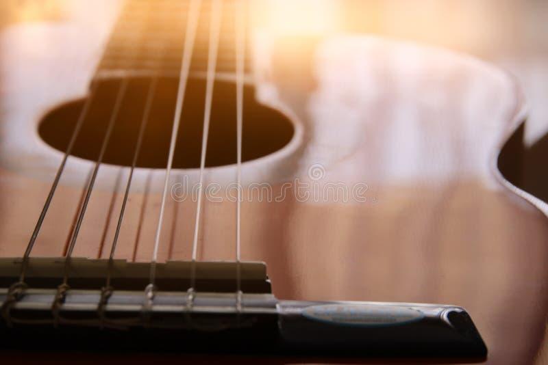 Zamyka up gitara akustyczna przeciw drewnianemu tłu zdjęcia stock
