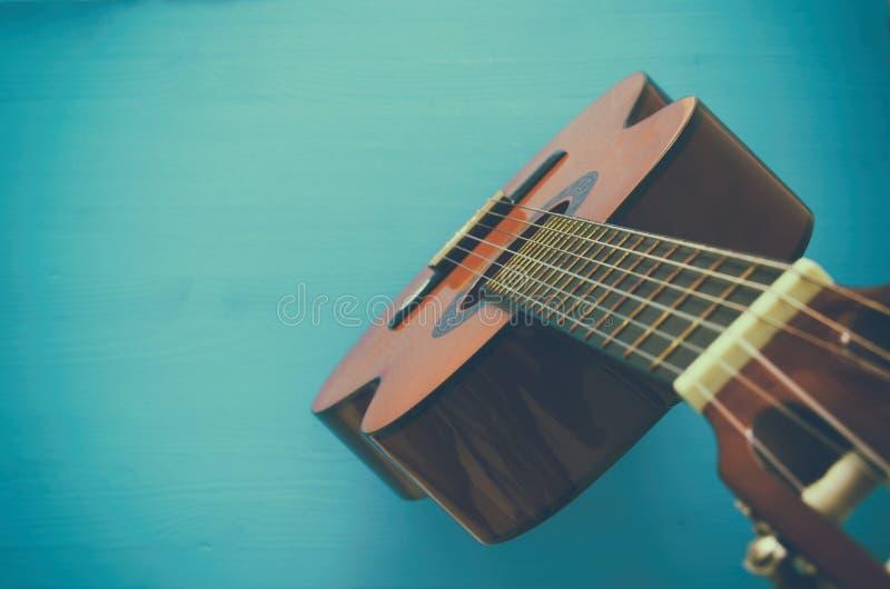 Zamyka up gitara akustyczna przeciw drewnianemu tłu obraz royalty free