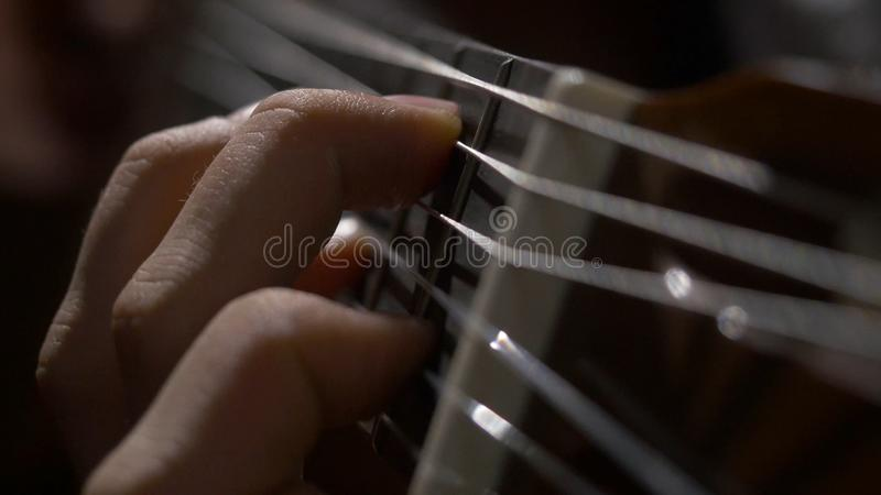 Zamyka up gitarzysta ręka bawić się gitarę akustyczną Zakończenie up strzelał mężczyzna z jego palcami na gryźć gitara obrazy stock