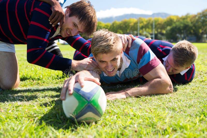 Zamyka up gracze bawić się rugby podczas gdy kłamający przy trawiastym polem fotografia stock
