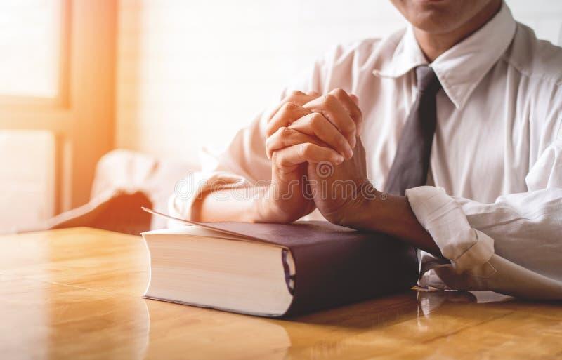 Zamyka up i ono modli się dla błogosławieństw od pastor kłaść ręki na czarnej książce biblia, buddysta, katolik, chrześcijanin, m fotografia royalty free