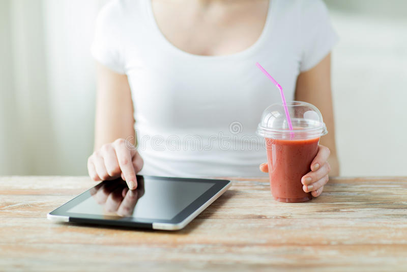 Zamyka up kobieta z pastylki smoothie i komputerem osobistym obraz royalty free