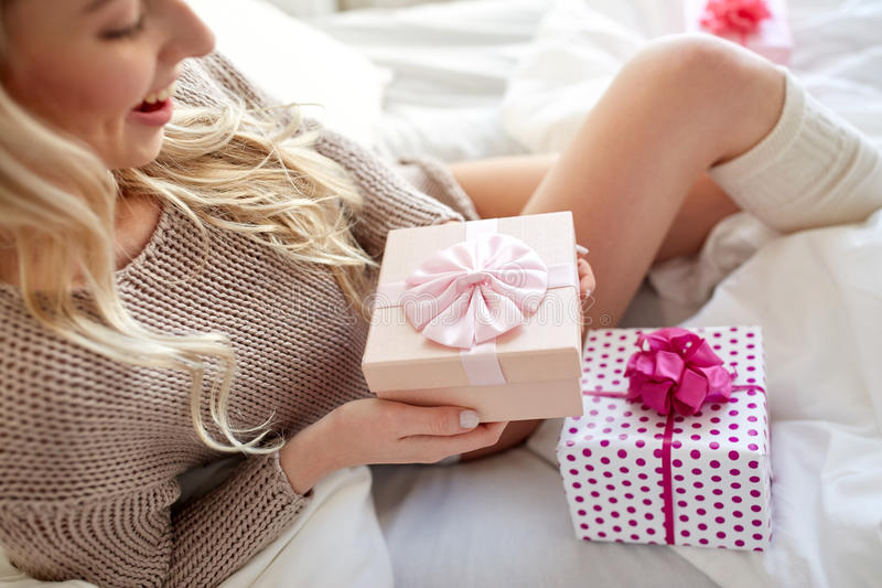 Zamyka up kobieta z urodzinowymi prezentami w łóżku obrazy royalty free