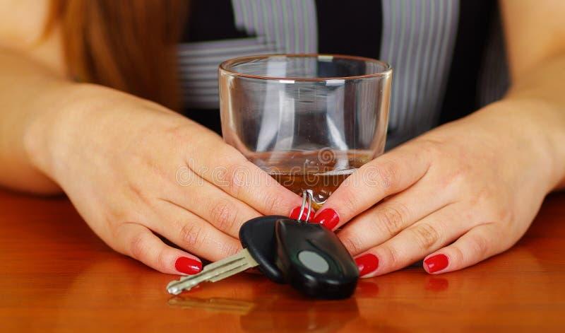 Zamyka up kobiety mienie z oba rękami szkło whisky i samochodu klucze nad drewnianym stołem, zdjęcie royalty free